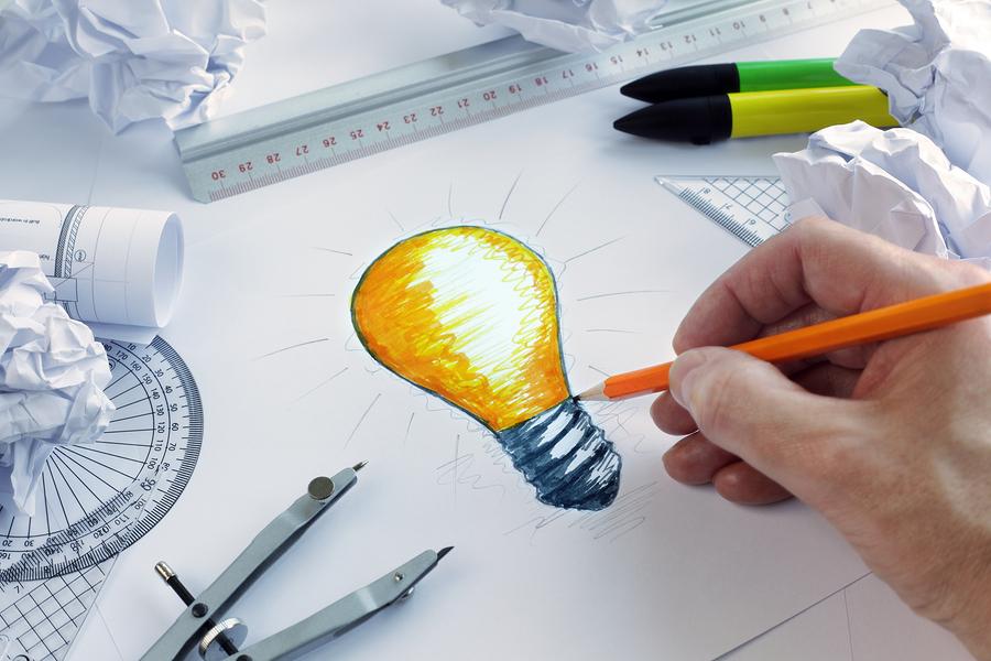 Designer desenhando uma lâmpada incancencente, conceito para um brainstorming e inspiração